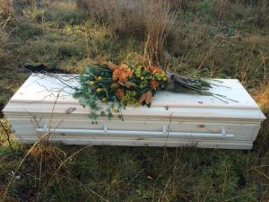 An image of simple pine box coffin