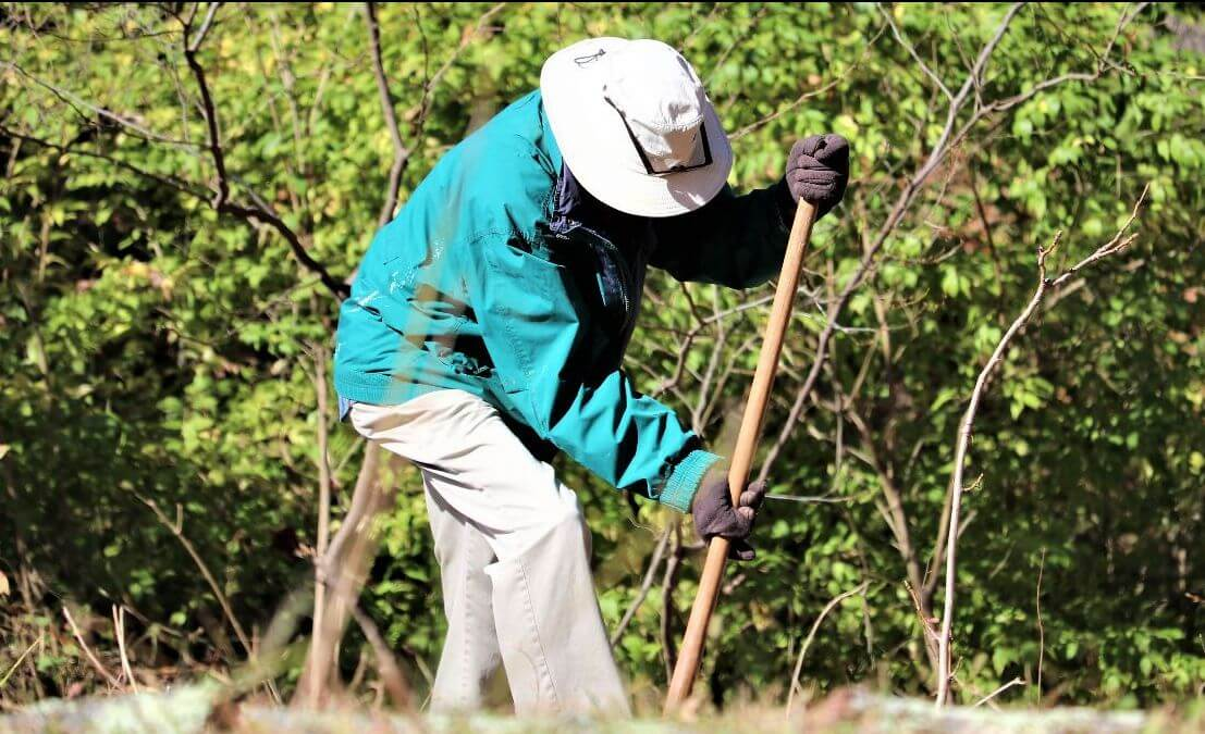 A man in a teal jacket and tan hat plants a tree at Heritage Acres